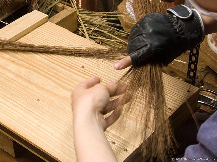 革手袋をして棕櫚箒作り